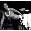 Beautiful woman workout with dumbbell on the bench in gym